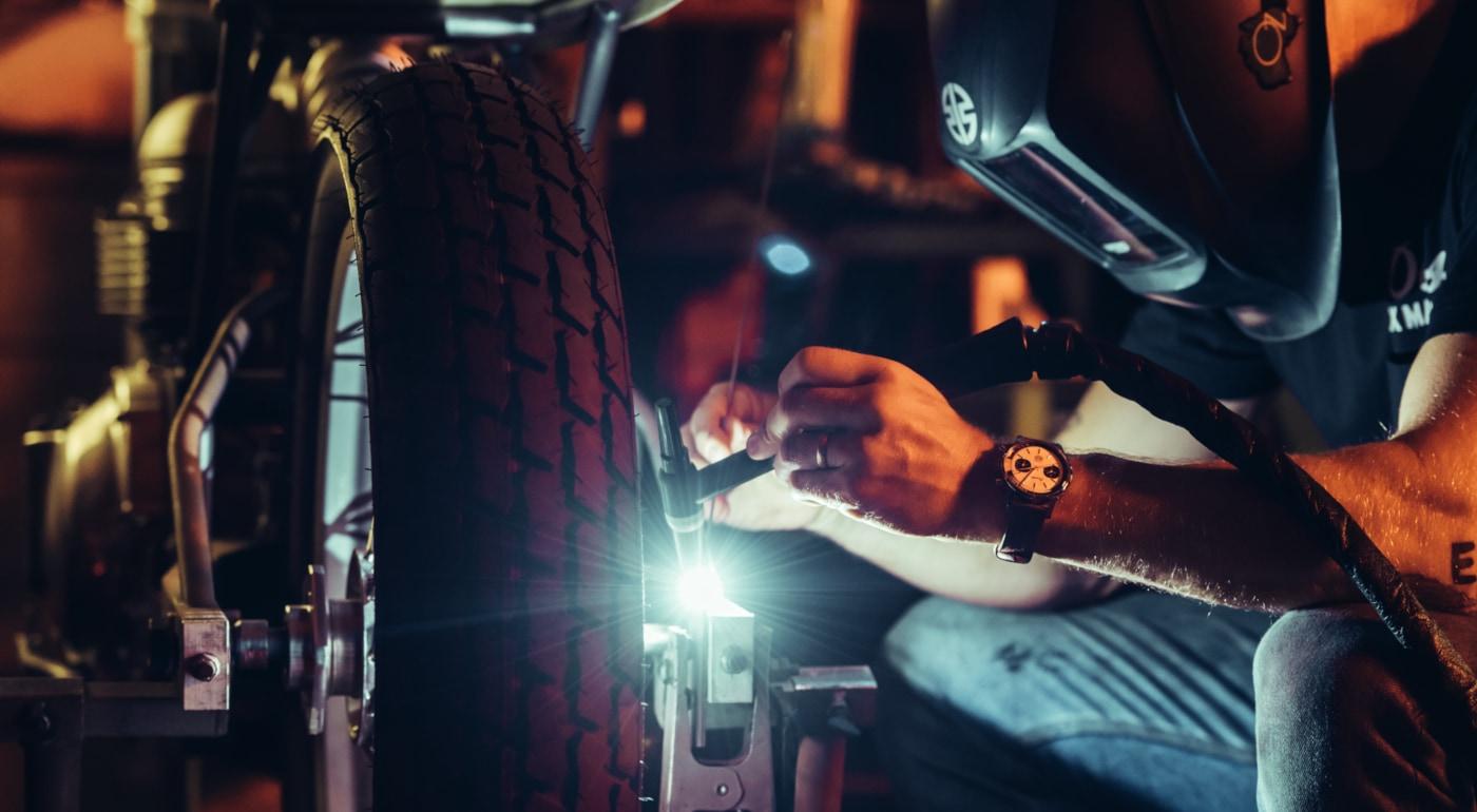 Welder working on a motorcycle wearing a Breitling watch